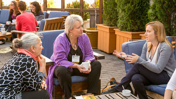 GEO members talk outside at a GEO conference