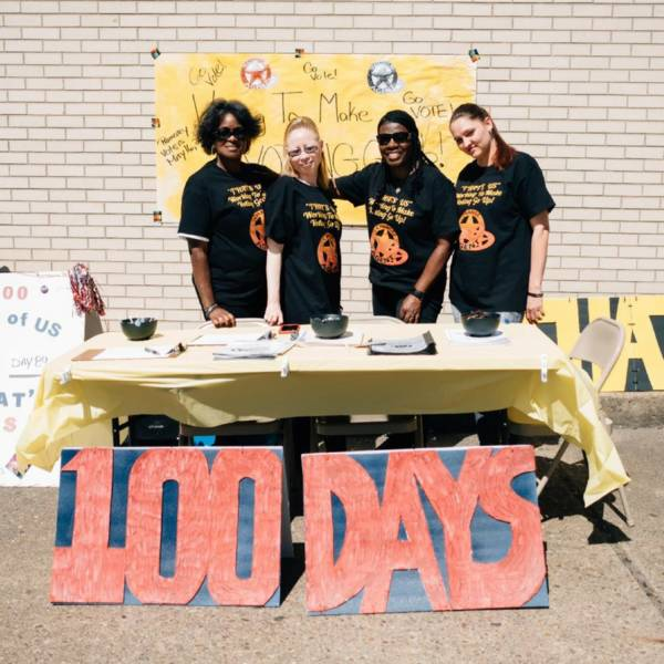 "This image shows four women in black ""Change Agent"" tshirts. They are standing behind a table and have signs reading ""100 Days"" and ""That's US"". They also have signs encouraging people to ""Go Vote!"""