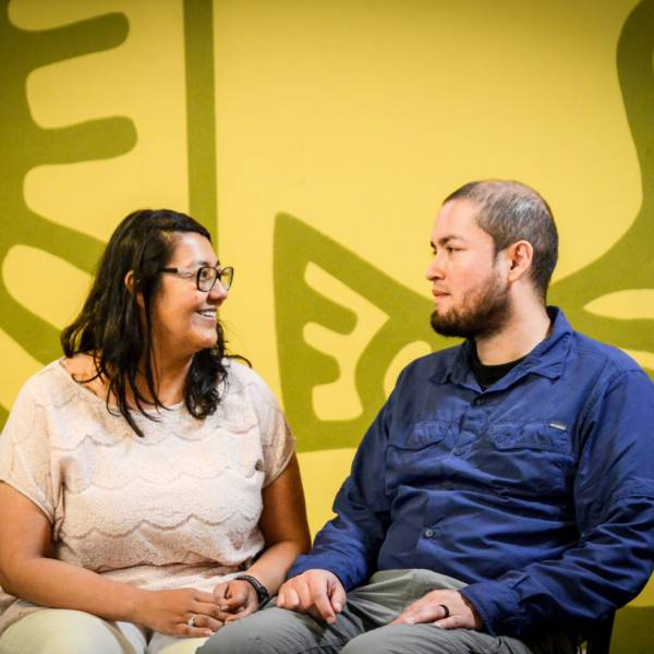 This image is of a man and a woman facing each other seated. They are in front of a yellow background with a gray design. The woman is smiling.