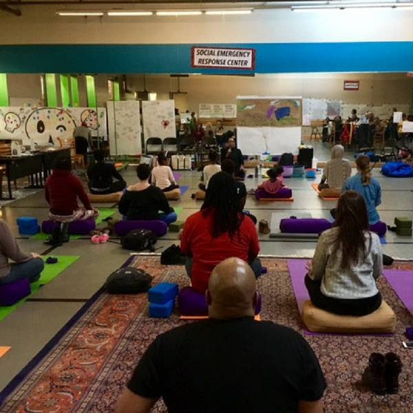 "Thisis an image looking at the back of several people doing yoga. There is a large mirror in the front. On the mirror is a sign that says, ""Social Emergency Response Center""."