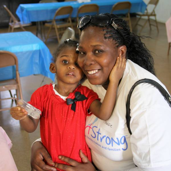 This image is of a woman and a young child. The child is sitting on the woman's lap, and they are hugging each other as they look at the camera.
