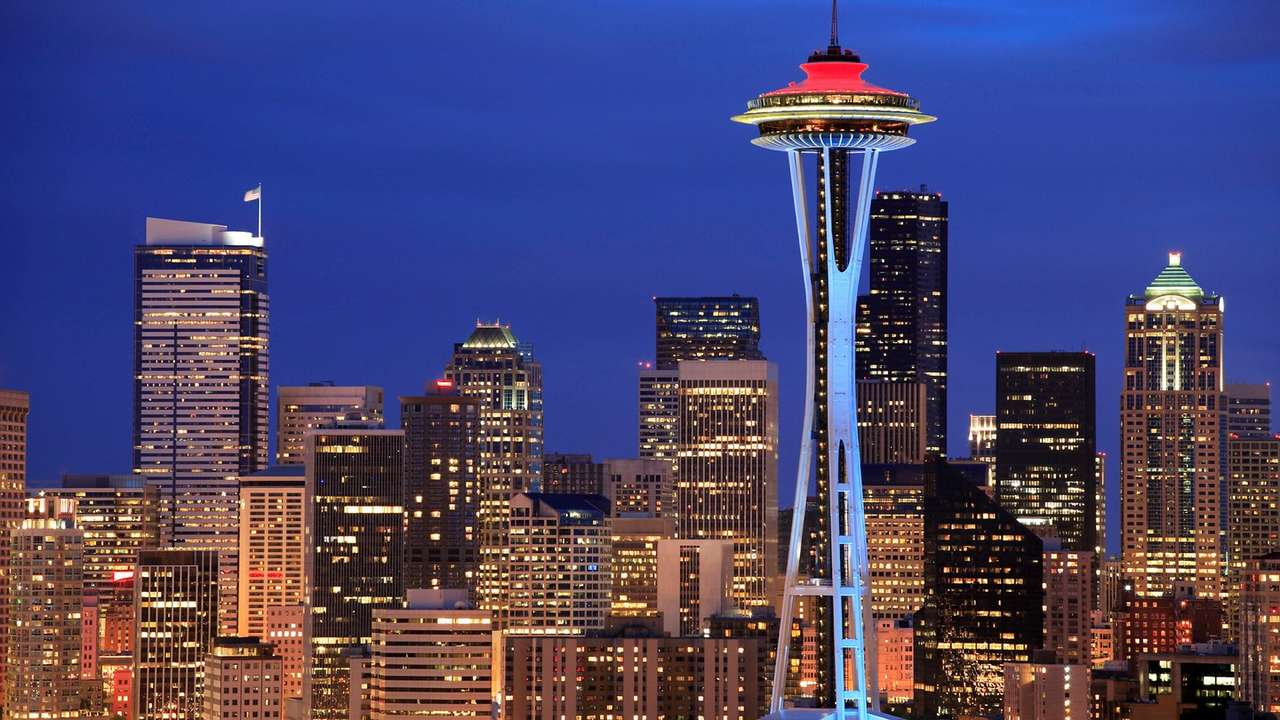 A photo of the Seattle Skyline from The Westin Seattle's website. There is an array of buildings lit up at night with the Space Needle in the foreground.